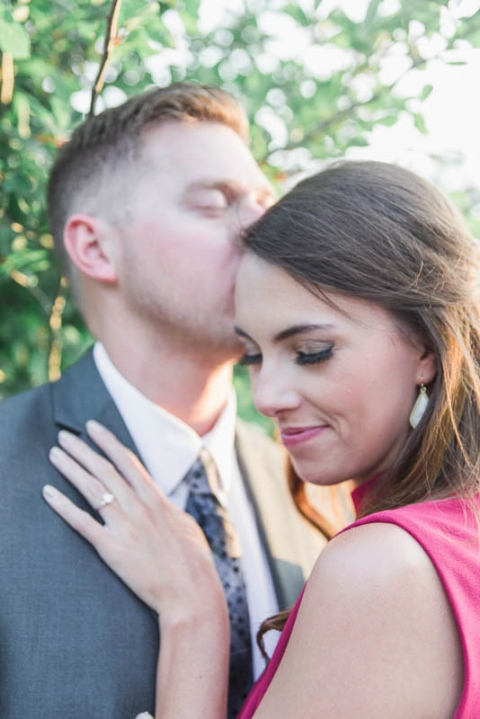 groom kisses brides head in their engagement photos